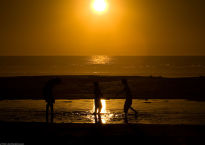 Three_children_play_in_a_lagoon_formed_from_high_tide_on_Morro_Strand_State_Beach_at_sunset